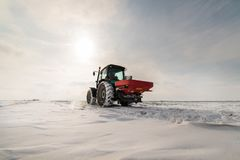 Farmer with tractor seeding - sowing crops at agricultural field. S in winter - snow Stock Photography