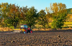 Farmer with tractor seeding. stock images