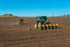 Farmer with tractor seeding - sowing crops at agricultural fields in spring. Selective focus, copy space Royalty Free Stock Photo