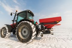 Farmer with tractor seeding - sowing crops at agricultural field. S in winter - snow Stock Photo
