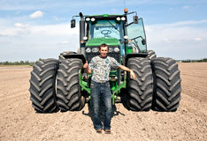 Farmer with tractor showing OK gesture Stock Photo