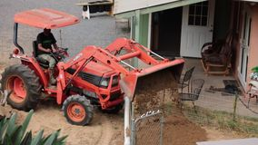 Farmer on tractor unloading sand into barn. Machinery in agricultural work tractor stock footage