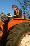 Farmer on tractor working on laptop computer Stock Image