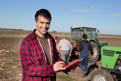 Farmer with tractors on field. Young handsome farmer standing on farmland. Workers and tractors in background Stock Photos