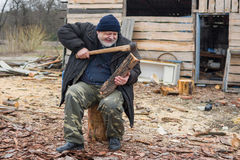 Farmer is trying to pull out an axe from log Royalty Free Stock Photos