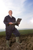 Farmer using laptop in ploughed field Stock Images