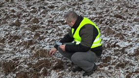 Farmer using tablet PC on frozen field stock video
