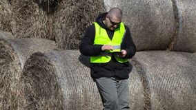 Farmer using tablet PC near the hay bales stock video