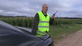 Farmer using walkie talkie near corn field stock video footage
