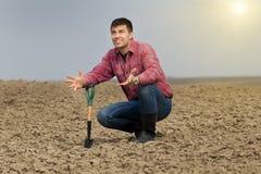 Farmer waiting for rain. Desperate farmer holding shovel on farmland and looking in sky Stock Photography