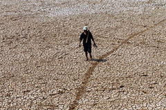 Farmer walking among the soil dries out due to a prolonged droug Royalty Free Stock Photo