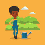 Farmer with watering can at field. Royalty Free Stock Photography