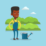 Farmer with watering can at field. An african-american happy farmer standing near a watering can on the background of agricultural field with green bushes. Man Stock Photos