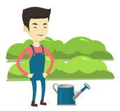 Farmer with watering can at field. Asian farmer standing near watering can on the background of agricultural field with green bushes. Young farmer watering Royalty Free Stock Image