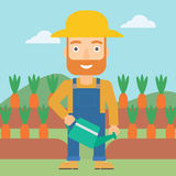 Farmer with watering can. A hipster man with the beard holding a watering can on the background of carrots growing on field vector flat design illustration Royalty Free Stock Images