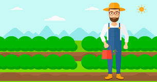 Farmer with watering can. A hipster man with the beard holding a watering can on the background of field rows with green bushes vector flat design illustration Stock Image