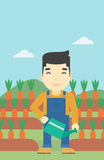 Farmer with watering can vector illustration. An asian farmer holding a watering can. Farmer watering carrots. Farmer standing on the background of carrots Royalty Free Stock Image