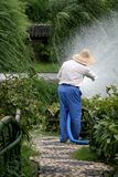 Farmer watering crops. In chinese garden Stock Photo