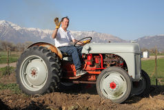 Farmer waving. Senior aged man riding on a farm tractor and waving to camera Royalty Free Stock Image