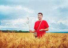 Farmer in a wheat field. Attractive smiling farmer standing in a wheat field, dramatic sky Royalty Free Stock Image