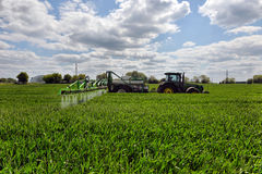 Farmer wheat field spraying herbicides Royalty Free Stock Image