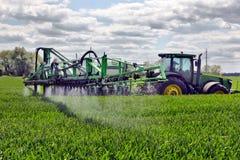 Farmer wheat field spraying herbicides Stock Image
