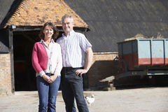 Farmer And Wife Standing In Front Of Farm Building Stock Photo