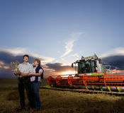 Farmer and wife standing next to combine harvester in wheat field Royalty Free Stock Photography