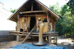 Farmer winnow rice at house on stilts Royalty Free Stock Image