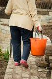 Farmer woman carrying a bucket walking outdoor stock photography