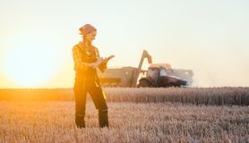 Farmer woman and combine harvester on wheat field royalty free stock photo