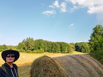 A farmer woman in a hat stands at a stack of fresh hay. After harvesting wheat and smile royalty free stock images