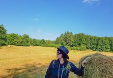 A farmer woman in a hat stands at a stack of fresh hay. A farmer woman in a hat looking in the field with stacks of fresh hay after harvesting wheat stock photos