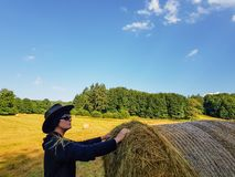 A farmer woman in a hat stands at a stack of fresh hay. A farmer woman in a hat stands near a stack of fresh hay after harvesting wheat royalty free stock images