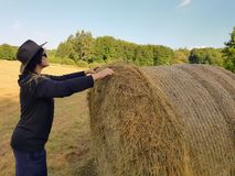 A farmer woman in a hat stands at a stack of fresh hay. A farmer woman in a hat stands near a stack of fresh hay after harvesting wheat stock photos