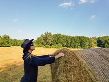 A farmer woman in a hat stands at a stack of fresh hay. A farmer woman in a hat stands near a stack of fresh hay after harvesting wheat royalty free stock image