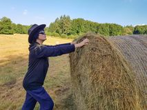 A farmer woman in a hat stands at a stack of fresh hay. A farmer woman in a hat stands near a stack of fresh hay after harvesting wheat stock photo