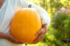 Farmer woman holding fresh pumpkin in hands. Stock Photo