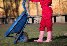 Farmer woman with wheelbarrow standing on farm. Farmer woman in red overalls and gumboots resting on ranch, leaning on wheelbarrow Stock Photos