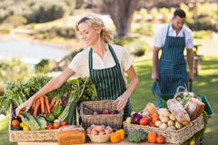 Farmer woman tidying up a table of local food Stock Photography