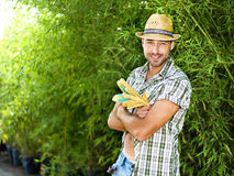 Farmer at work in a greenhouse. With gloves and straw hat Stock Photos