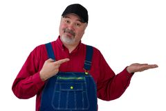 Farmer or worker pointing to his empty hand. Middle-aged farmer or worker wearing a denim bi overall pointing to his empty hand over white copy space with a stock photo