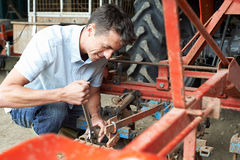 Farmer Working On Agricultural Equipment In Barn Royalty Free Stock Image