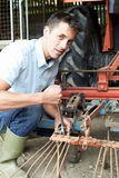 Farmer Working On Agricultural Equipment In Barn Royalty Free Stock Photography