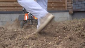 Farmer working in field. Man plowing the garden. Gimbal movement closeup shot stock video footage