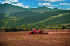 Farmer working the fields with tractor and plow. In summer Royalty Free Stock Photo