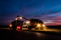 Harvester offloading grain into waiting truck at sunset, Illinois royalty free stock photo