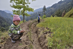 Farmer works soil  in mountainous area, next to boy Stock Photo