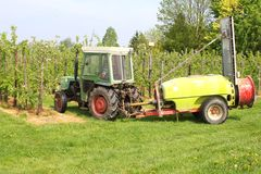 Farmer is working in the agricultural fruit orchards, Tricht / Betuwe, netherlands. Farmer works with tractor and machinery equipment in the fruit orchard in royalty free stock photos