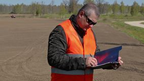 Farmer writing at the field where the tractor harrow the ground stock footage